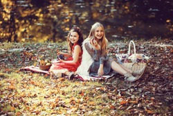 Two pretty laughing blonde and brunette girls in beautiful gowns with fruit in their hands and picnic baskets sitting on plaid on lake shore in autumn park, horizontal picture