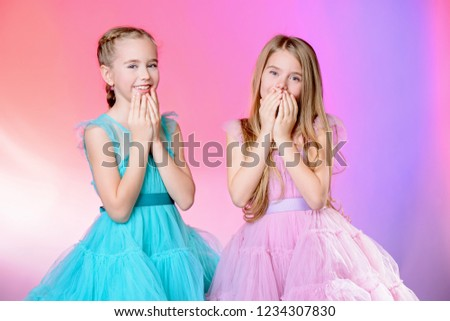 Two pretty little girls dressed in beautiful festive dresses. Kid's fashion concept. #1234307830