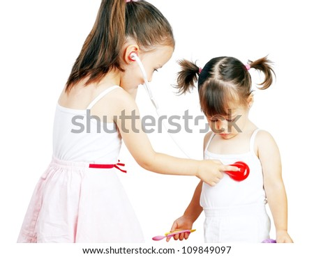 Two pretty little girls playing doctor