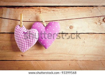 Two pretty pink material Valentine hearts hanging on a line with clothes pags over wooden boards.