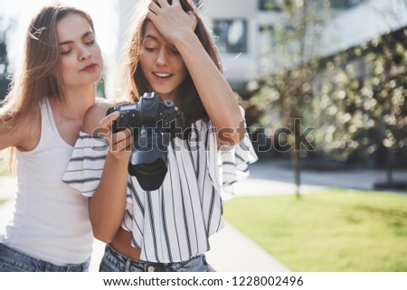 Two pretty pretty friends of the girl with the camera take photos together and walk in the city.
