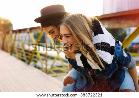Two pretty sisters hipster girls hugs and having fun together, wearing trendy clothes, positive emotions, bright colors