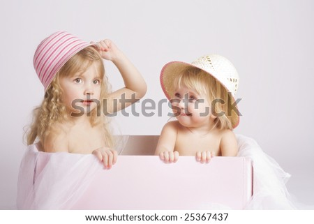 Two pretty sisters of 2 and 4 years old in summer bonnets sitting in big pink box