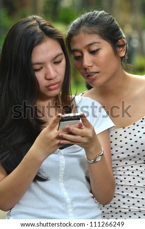 Two pretty southeast asian girls looking and sharing information on a smartphone with curiosity