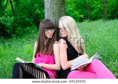 two pretty student girls reading books in park