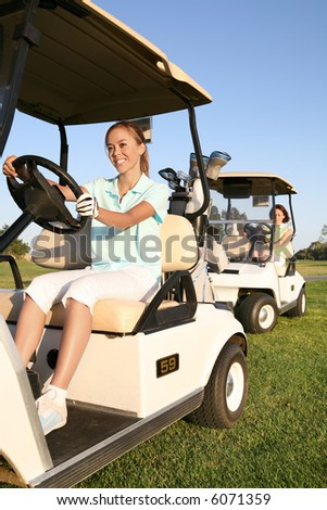 Two pretty women golfers driving in the golf carts