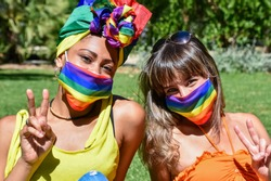 Two pretty women of different race (female friends or lgbt couple) wearing rainbow headdress and rainbow face masks make victory sign with hand. LGBT pride day celebration in pandemic times.
