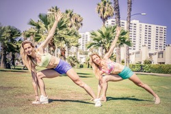 Two pretty women stretching in a park before starting a workout session - Girls doing gymnastics exercises outdoors