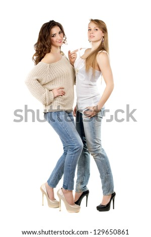 Two pretty women wearing blue jeans and heels. Isolated on white