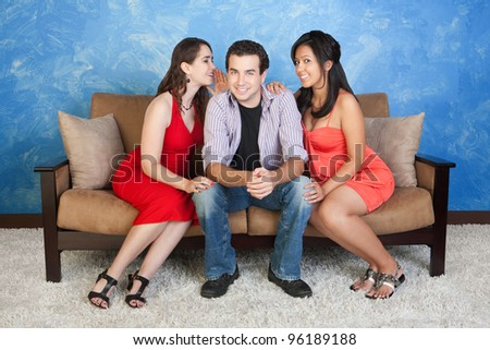 Two pretty women whisper and flirt with handsome man
