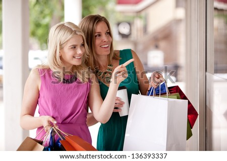 Two pretty women windows shopping in a down town city