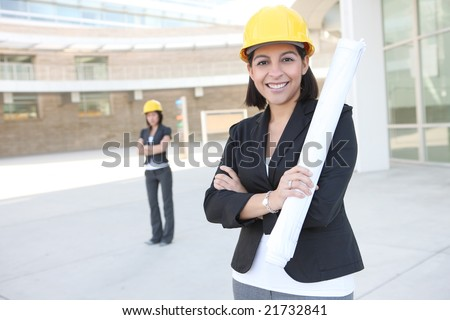 Two pretty women working as architects on a construction site - stock photo