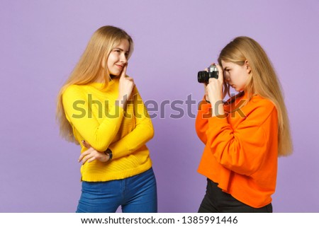 Two pretty young blonde twins sisters girls in colorful clothes taking pictures on retro vintage photo camera isolated on violet blue background. People family lifestyle concept. Mock up copy space