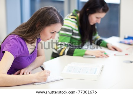 two pretty, young college students in a library (shallow DOF; color toned image)