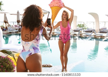 Two pretty young girlfriends taking pictures while posing at the swimming pool resort spa