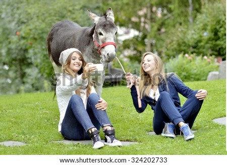Two pretty young girls in autumn clothes taking a funny selfie with a hilarious Donkey. Concept of freedom and love for animals. Best Friend taking photo with smart phone of herself and a donkey.