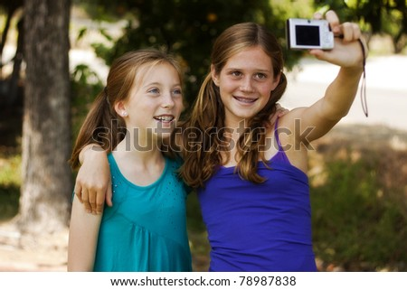 two pretty young girls posing for a picture