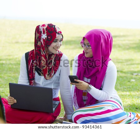 Two pretty young Muslim lady in conversation while shown something in smartphone.
