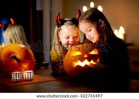 Two pretty young sisters in halloween costumes carving a pumpkin together on Halloween