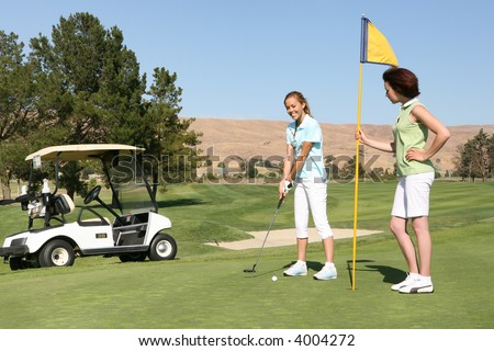 Two pretty young woman golfing on the course