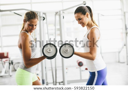 Two pretty young women having dumbbells workout in the gym #593822150