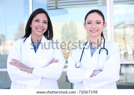 Two pretty young women nurses outside hospital smiling