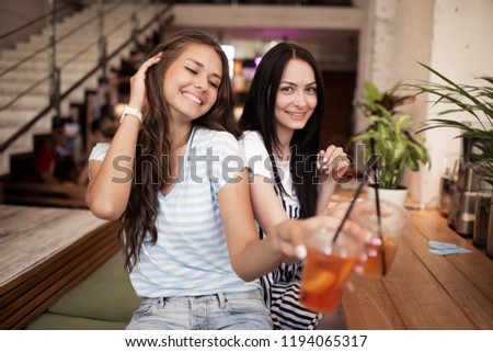Two pretty youthful smiling girls,dressed in casual outfit,sit next to each other and look at the camera in a cozy coffee shop. #1194065317