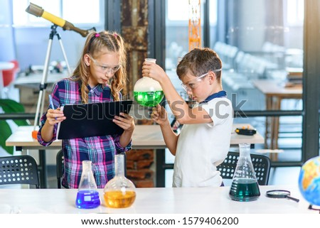 Two primary school pupils in protective goggles doing experiment with colored liquids in glass flasks and dry ice.