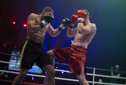 Two professional boxers in dynamic boxing action on the ring under lights of sport arena soffits. Boxer hit opponent