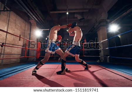 Two professional boxers training kickboxing in the ring at the health club