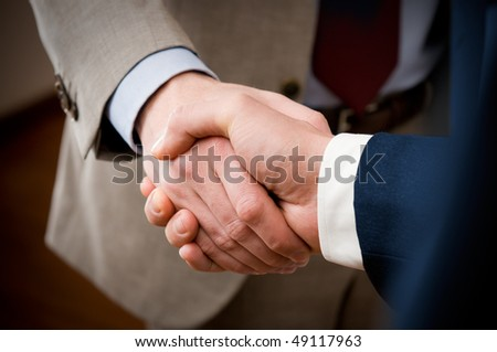 Two professional businessman giving handshake in the office, closeup selective focus