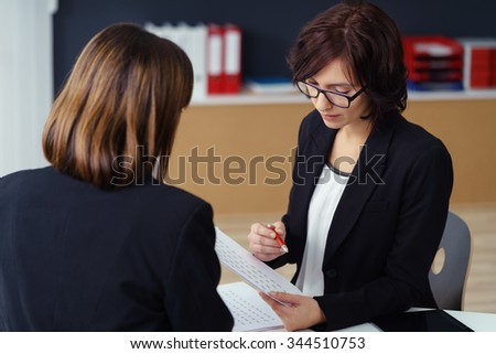 Two Professional Businesswomen in Black Suits Having a One-on-One Business Meeting Inside the Office.