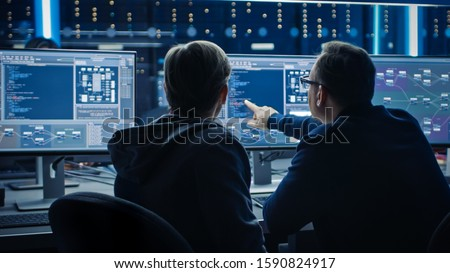 Two Professional IT Programers Discussing Blockchain Data Network Architecture Design and Development Shown on Desktop Computer Display. Working Data Center Technical Department with Server Racks