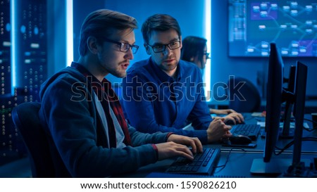 Two Professional IT Programers Discussing Technical Data Show on Desktop Computer Display. Working Data Center Technical Department with Server Racks in the Background