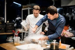 two professional male chefs preparing molecular cuisine dish in the kitchen. A lot of smoke and steam around them
