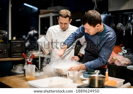 two professional male chefs preparing molecular cuisine dish in the kitchen. A lot of smoke and steam around them Stok fotoğraf ©