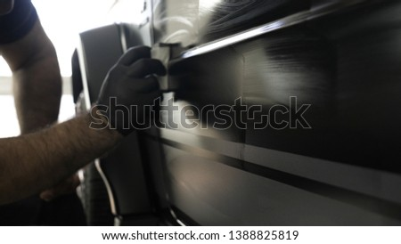 Two professional masters in car painting and ceramics overlay a layer of ceramics using a micro fiber and cloth, in a car deteyling center. Concept of: Service, New car, Refresh. #1388825819