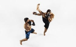 Two professional MMA fighters boxing isolated on white studio background. Top view of couple of muscular athletes. Sport, healthy lifestyle, competition, dynamic and motion, action concept. Copyspace.