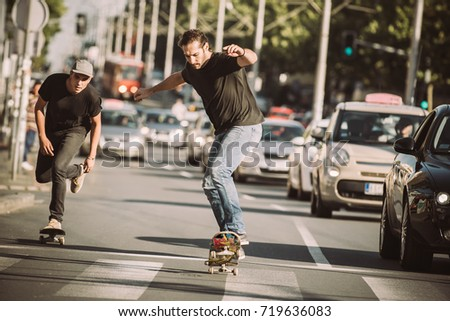 Two professional skateboarders riding skateboard slope on the capital city streets