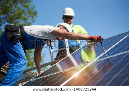 Two professional technicians installing solar photo voltaic panel to metal platform on blue sky background. Stand-alone solar system installation, efficiency and professionalism concept.