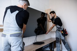 Two professional technicians, workers in uniform installing television on the wall indoors. Construction, maintenance and delivery concept. Selective focus on young man. Horizontal shot