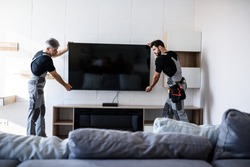 Two professional technicians, workers in uniform installing television on the wall indoors. Construction, maintenance and delivery concept. Selective focus. Horizontal shot