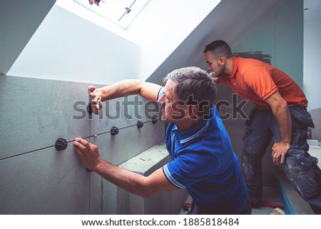two professional tilers installing large format tiles. home renovation concept Foto stock ©