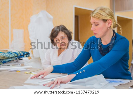 Two professional women tailors, designers discussing pattern of new couture collection at atelier, studio. Dressmaking, creativity and tailoring concept #1157479219