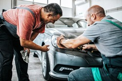 Two professional workers talking and checking car details during valeting and polishing procedure.