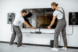 Two professional workmen in workwear installing a large TV monitor and audio system in the white living room. Home appliances installation concept