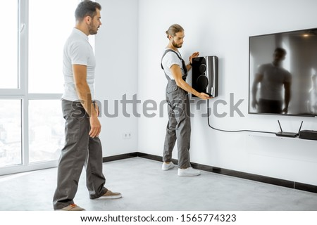 Two professional workmen in workwear installing luxury audio system in the white living room. Home appliances installation concept
