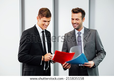 Two professionals talking and looking at files