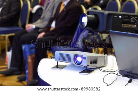 Two projectors on background of blur sitting people in bright conference hall
