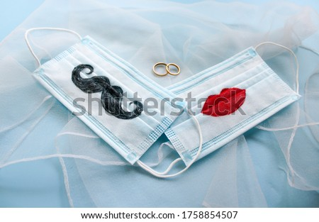 Two protective face masks with a mustache and lips painted on them and two wedding rings are on blue background. The concept of wedding ceremonies during a pandemic of coronavirus COVID-19
